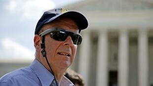 Un homme portant des Google Glass par dessus des lunettes de soleil.