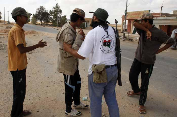 A Libyan rebel fighter (2nd R) turns back a trio of boys trying to volunteer to fight