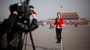 中国人大开幕期间一位记者在北京天安门广场做报道2013年3月5日