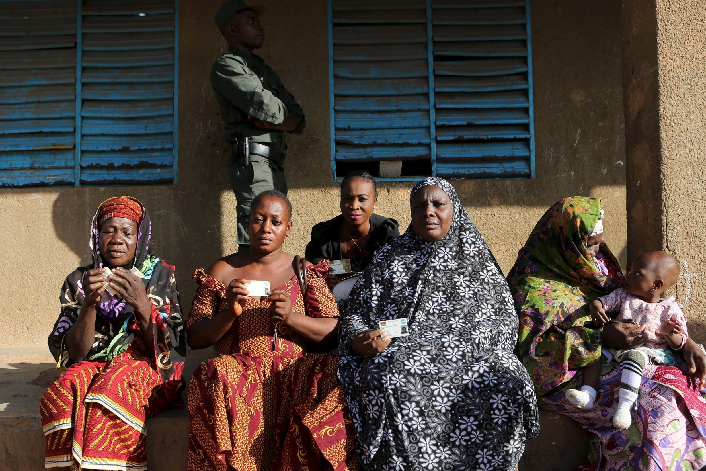 Ouagadougou: des femmes montrent leurs cartes d'électrices.