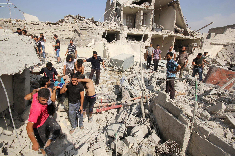 Les Syriens fouillent les décombres d'immeubles détruits lors d'une attaque aérienne du gouvernement sur le district rebelle d'Al-Maghair de la ville d'Alep, au nord de la Syrie, le 16 septembre 2015.