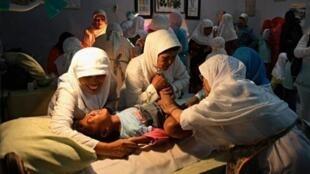 Des femmes pratiquent une excision sur une petite fille.