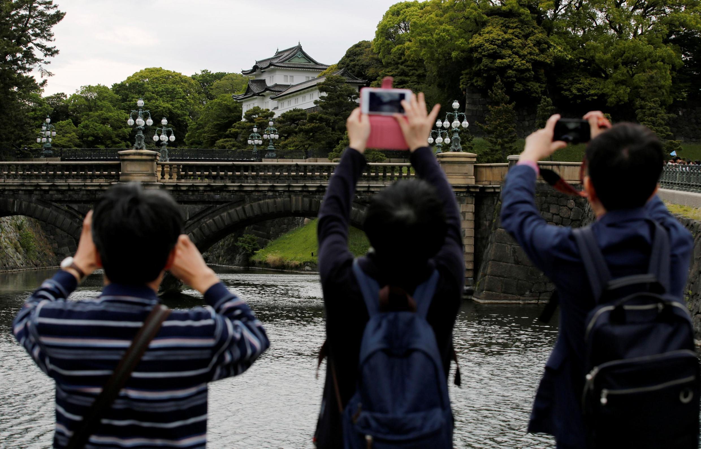 Visitantes tiram fotos do Palácio Imperial em Tóquio, Japão, 29 de abril de 2019.