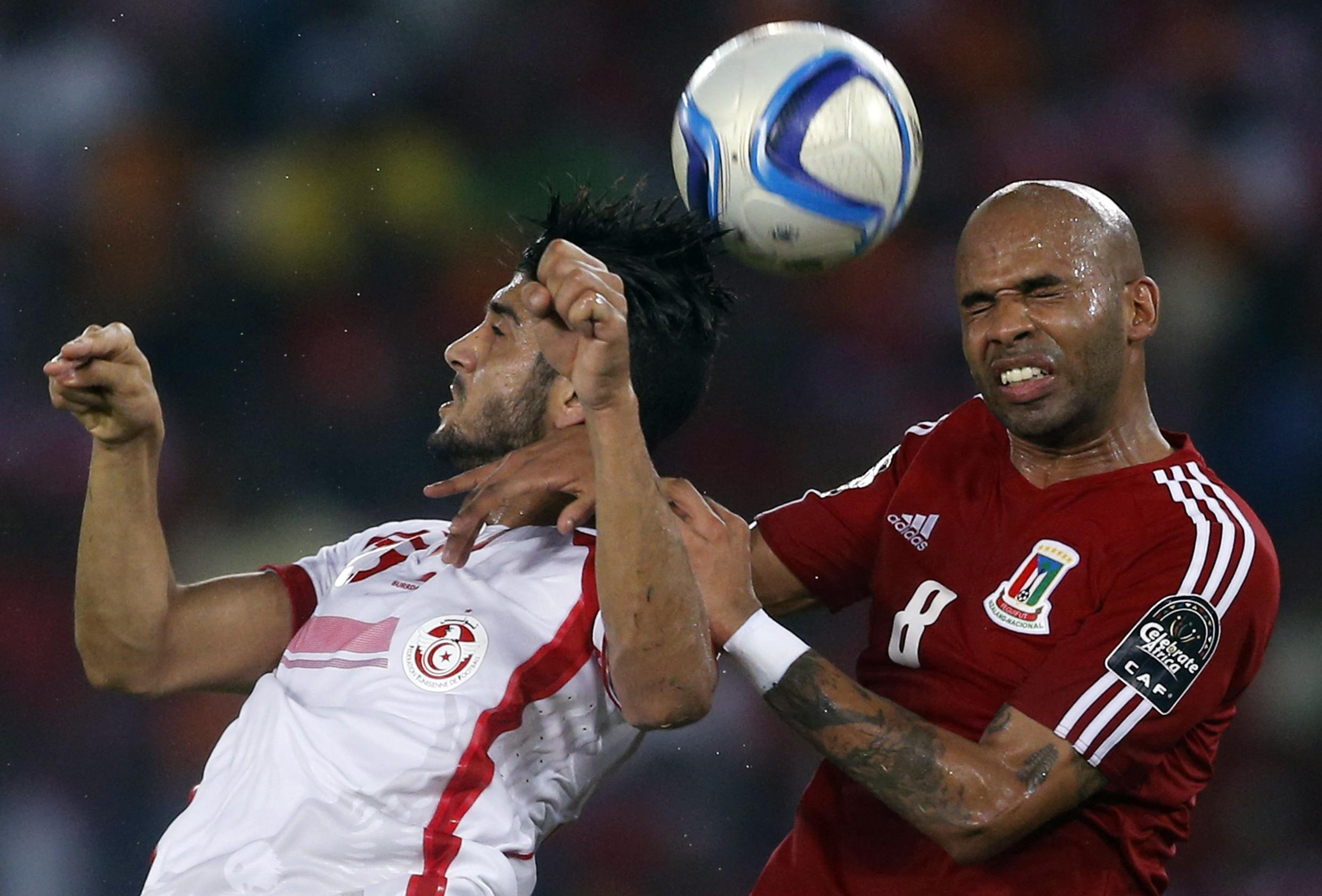 Equatorial Guinea's Iban Iyanga (R) fights for the ball with Ferjani Sassi of Tunisia during their quarter-final match in Bata