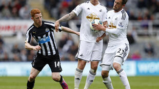Newcastle's Jack Colback (L) in action with Swansea's Jonjo Shelvey and Gylfi Sigurdsson