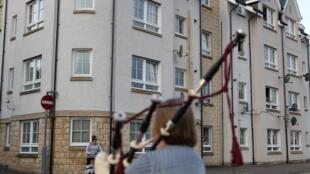 En Écosse, une femme joue de la cornemuse en soutien au personnel soignant de l'hôpital de Pitlochry le 23 avril 2020.