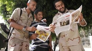 Rebeldes celebram a publicação de um anúncio de captura de Muammar Kadafi em jornais de Trípoli.