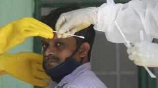 Unos trabajadores sanitarios reocgen una muestra de una persona en un centro de pruebas de COVID-19 en la ciudad india de Chennai el 26 de junio de 2020