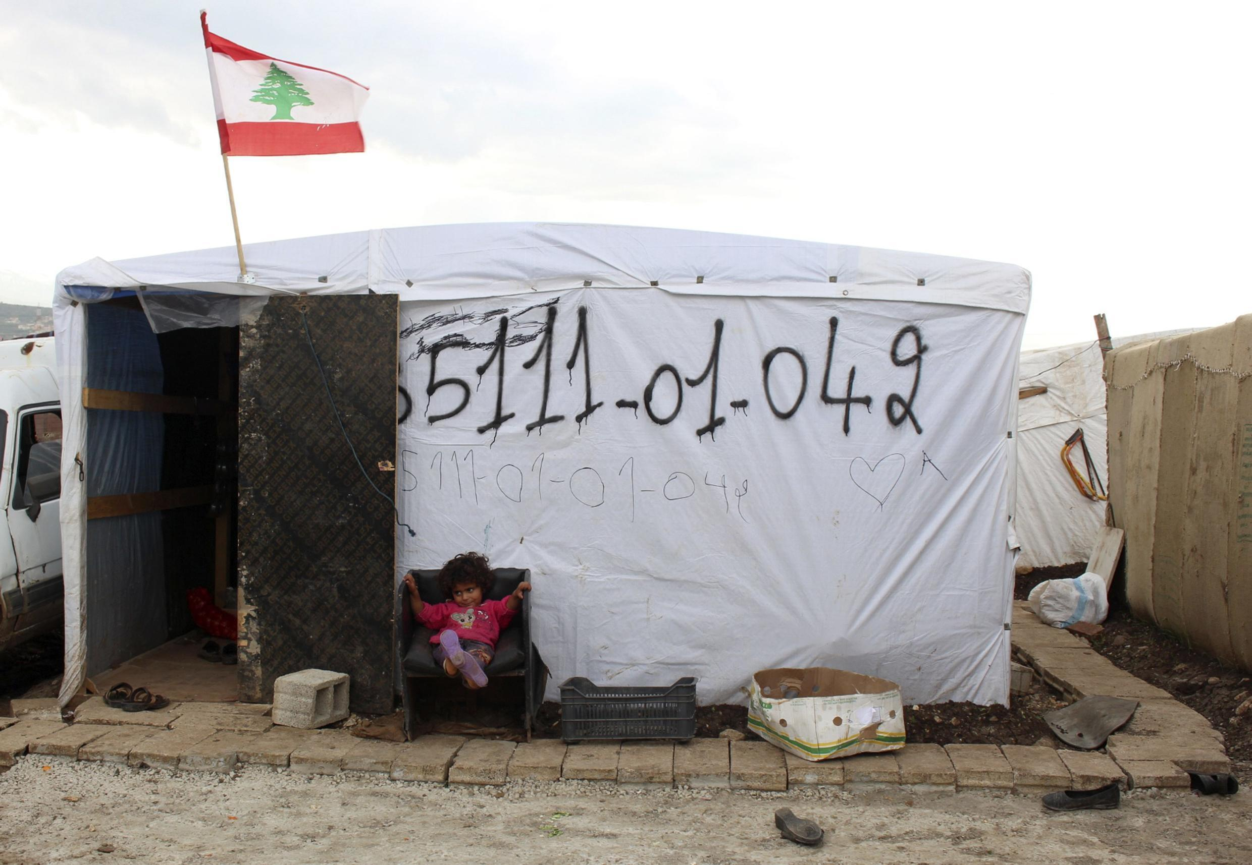 A Syrian refugee girl sits outside a tent at a refugee camp in Akkar, northern Lebanon, 9 December, 2014