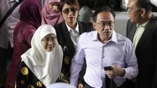 Le leader de l'opposition malaisienne Anwar Ibrahim, lors de son arrivée, accompagné de sa femme, à la Haute Cour de justice Wan Azizah, pour entendre le verdict de son procès, le 9 février 2015.