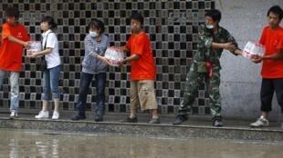 中国甘肃南部舟曲泥石流灾区民众互相传递水箱,2010年八月十二日。