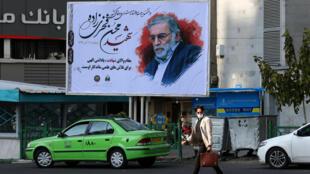 Un hombre pasa frente a un cartel con la imagen del científico asesinado Mohsen Fakhrizadeh, el 30 de noviembre de 2020 en una calle de Teherán
