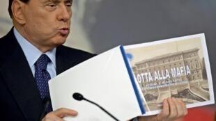 Silvio Berlusconi montre un livre intitulé « Lutte contre la Mafia », durant une conférence de presse à la Villa Chigi, à Rome, le 9 octobre 2009.