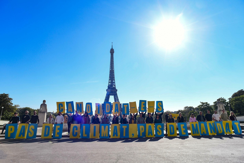 """Unos activistas de las ONG Greenpeace, Fundación Nicolas Hulot, Oxfam y Notre Affaire a Tous, sostienen una pancarta con el mensaje """"Candidatos. Sin clima, sin mandato"""", el 14 de octubre de 2021 en París"""