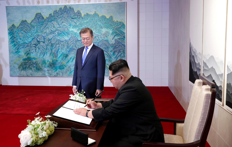 Tổng thống Hàn Quốc Moon Jae In đứng nhìn lãnh đạo Bắc Triều Tiên Kim Jong Un ghi sổ lưu niệm tại Nhà Hòa Bình, Bàn Môn Điếm, ngày 27/04/2018