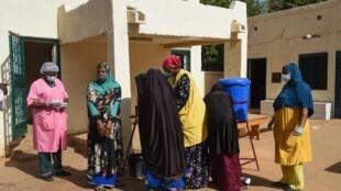 Des visiteurs se lavent les mains à l'entrée de la maternité Issaka Gazoby de Niamey, le 8 mai 2020;