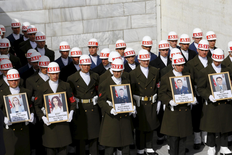 Члены почетного караула держат фотографии погибших в результате теракта, Анкара, 19 февраля 2016.