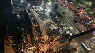 Des secouristes, équipés de lampes frontales, progressent difficilement dans les décombres de l'hôtel effondré, à Quanzhou le 7 mars 2020.