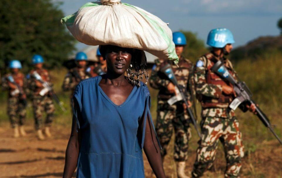 Mkimbizi akiandamana na askari wa kulinda amani, karibu na kambi ya kulinda raia (POC) ya Umoja wa Mataifa mjini Juba, Oktoba 4, 2016.