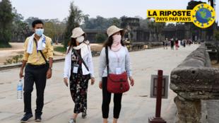 Des touristes portent des masques lors de leur visite du temple d'Angkor Wat au Cambodge, le 6 mars 2020.