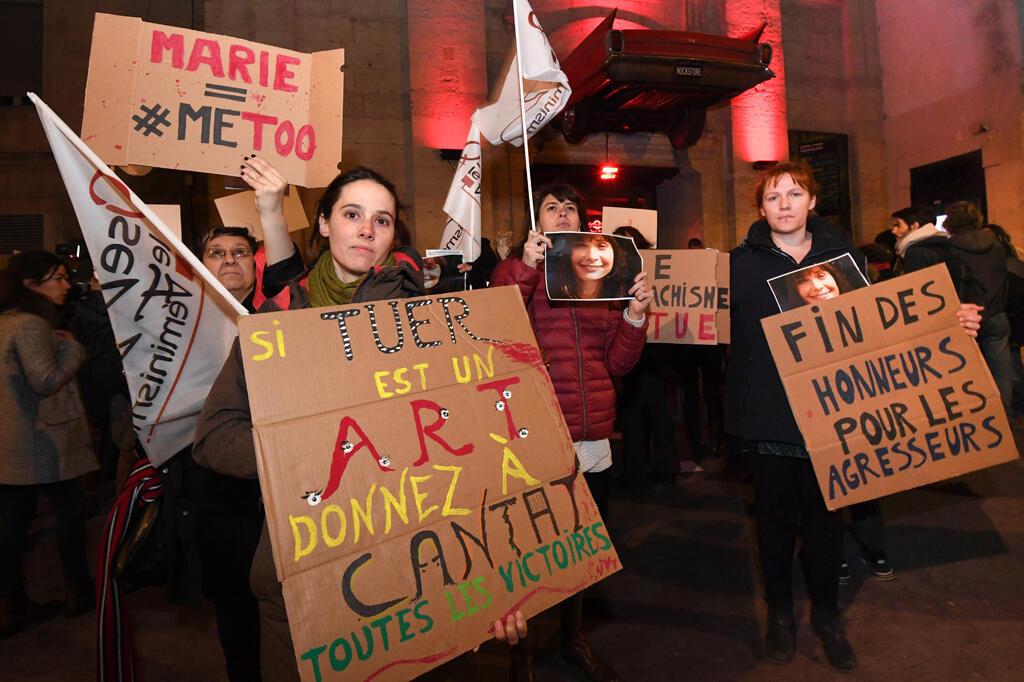 """Mulheres de organizações feministas protestam com cartazes e fotos de Marie Trintignant com os dizeres: """"Se matar é uma arte, deem a vitória Cantat, """"Machismo mata"""" e """"Fim das honras para os agressores"""" em frente ao Rockstore em Montpellier 12/03/18"""