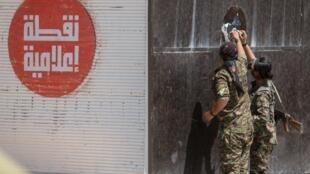 Soldats kurdes retirant une affiche collée par l'Etat islamique dans la ville de Tal-Abyad en Syrie, le 16 juin 2015 (image d'illustration).