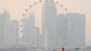 人们从新加坡摩天轮附近拍摄烟雾笼罩景观   2016年8月26日