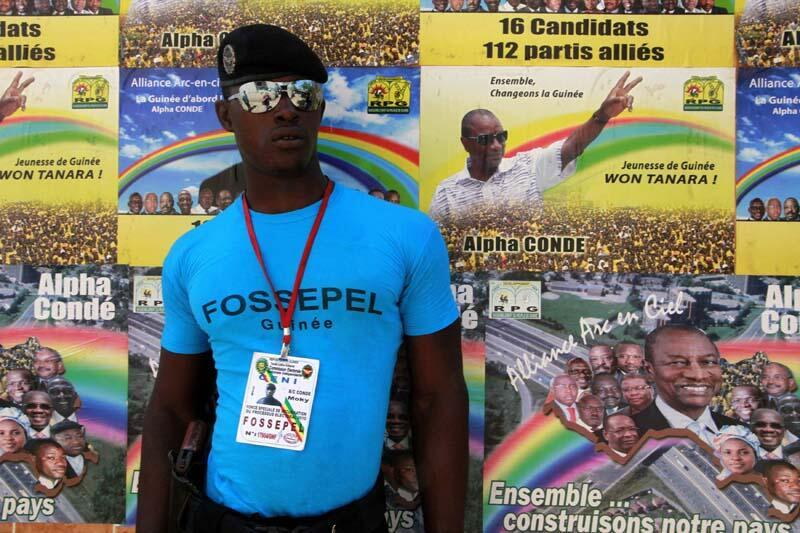 A soldier stands near election posters at the party headquarters of RPG presidential candidate Alpha Conde in Conakry