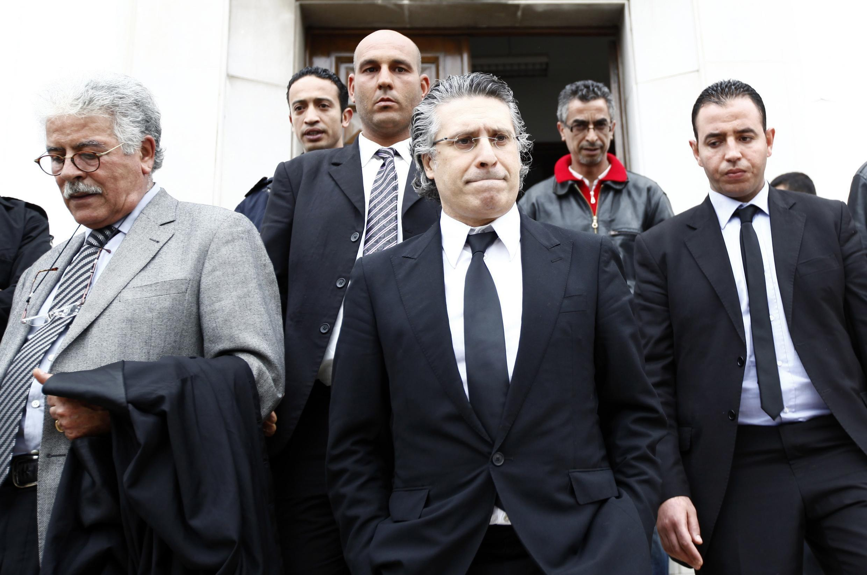 Глава телекомпании Несма ТВ Набил Каруи (Ц) после заседания суда в Тунисе 19/04/2012