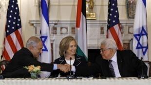 Benjamin Netanyahu (à esq.) e Mahmoud Abbas  (à dir.) trocam aperto de mão diante de Hillary Clinton, em Washington.