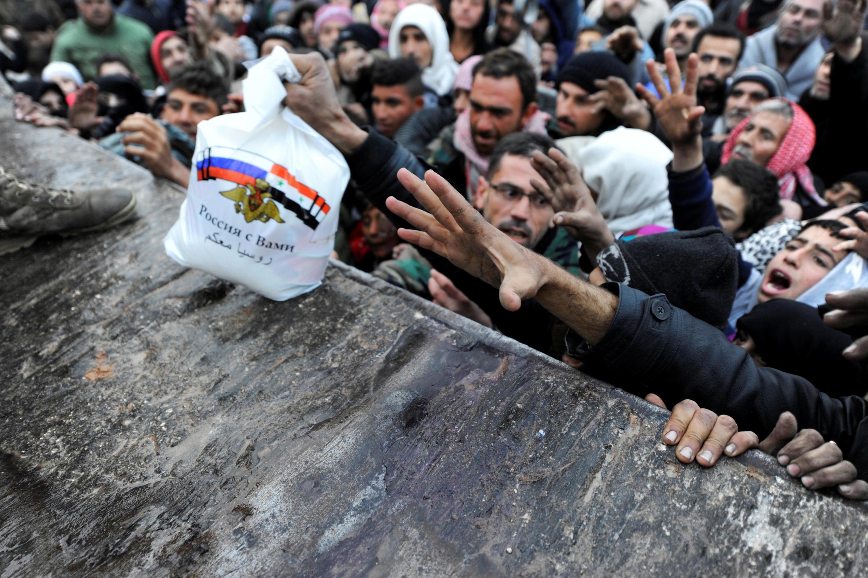 Российские военные раздают продукты питания сирийцам, эвакуированным из восточной части Алеппо, 30 ноября 2016.