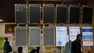 Varios viajeros pasan frente a unos paneles informativos de la Terminal 4 del aeropuerto de Barajas, el 23 de marzo de 2021 en Madrid
