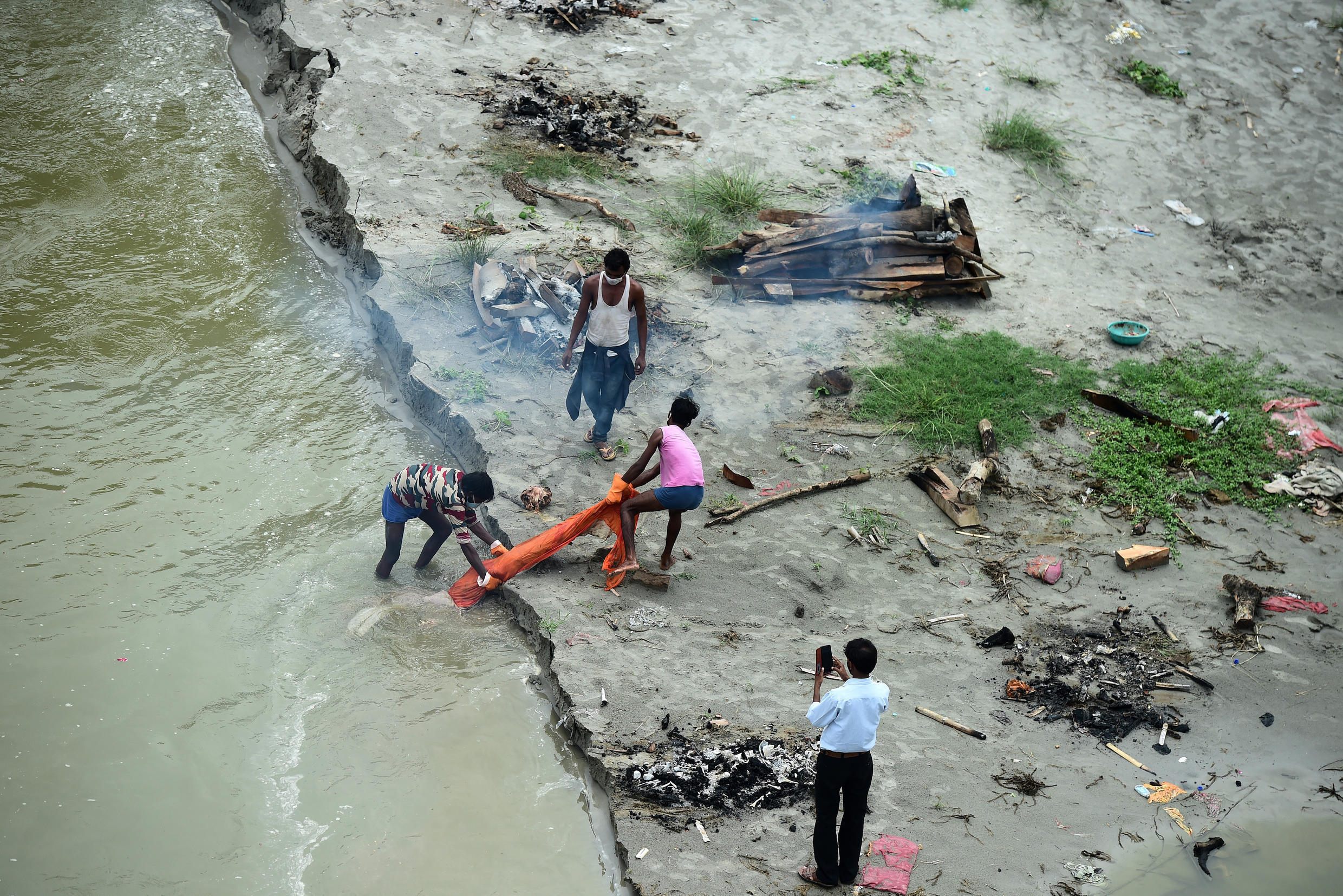 Annual monsoon rains are swelling the Ganges, washing away the sand and revealing corpses