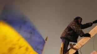 Un manifestant pro-européen construit une barricade sur la place de l'Indépendance à Kiev, le 12 décembre.