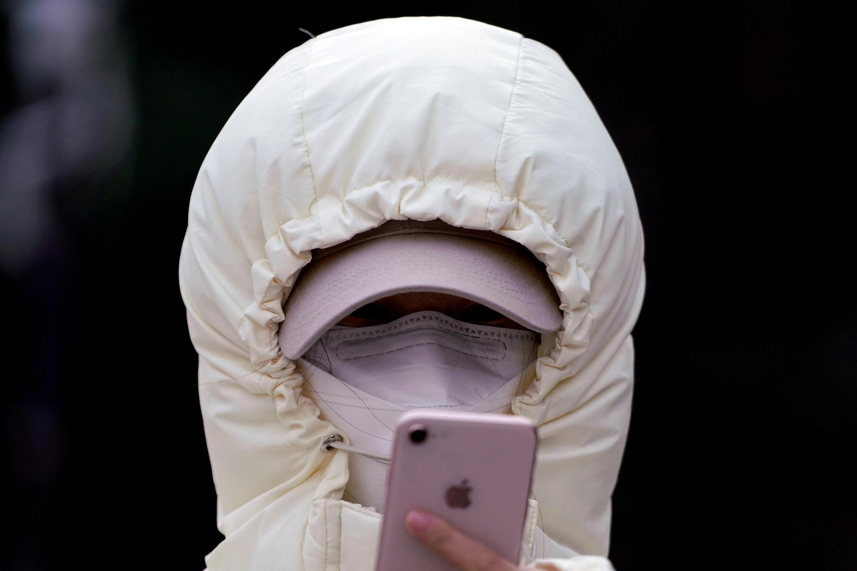 Một phụ nữ tại Thượng Hải (Trung Quốc) đeo khẩu trang, đang kiểm tra điện thoại của mình. Ảnh chụp ngày 29/01/2020.
