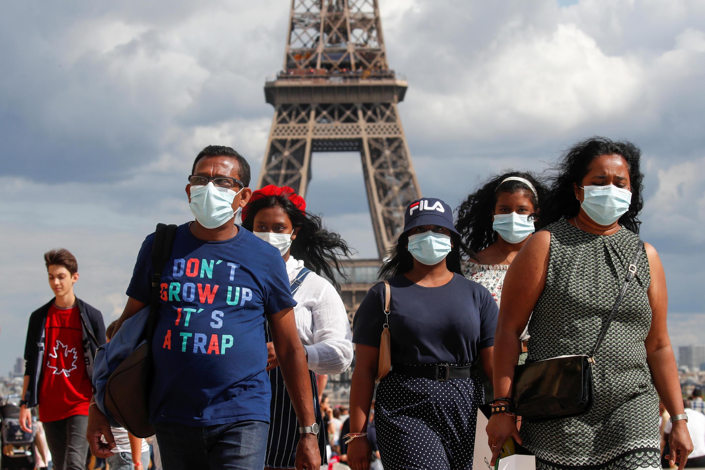 埃菲尔铁塔前戴口罩的人群