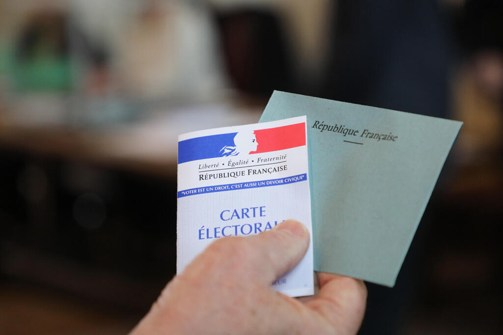 A voter holds an elector's card and a ballot envelope at a European election voting station at the town hall of Le Touquet in northern France, 26 May 2019.