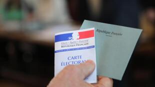 Une personne tient sa carte électorale et une enveloppe pour voter aux élections européennes dans le bureau de vote de la mairie du Touquet, dans le nord-ouest de la France, le 26 mai 2019.