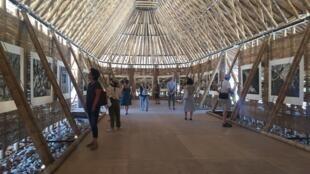 Interior da maloca de bambu com fotos de Matthieu Ricard.