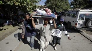 Des Haïtiens transportent une femme blessée dans une rue de Port-au-Prince.