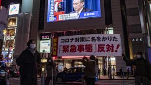 Les images du Premier ministre japonais Yoshihide Suga déclarant un nouvel état d'urgence sur un écran géantdans une rue de Tokyo, le 7 janvier 2020