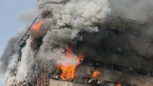 Um edifício de 15 andares no qual dezenas de bombeiros tentavam apagar um incêndio desabou nesta quinta-feira em Teerã, segundo imagens transmitidas ao vivo pela televisão pública iraniana.