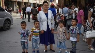 (FILES) This file photo taken on June 4, 2019 shows a Uighur woman waiting with children on a street in Kashgar in China's northwest Xinjiang region.