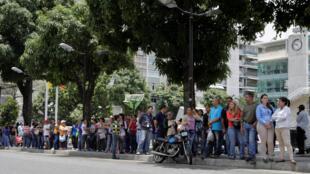 Des habitants de Caracas attendent de pouvoir entrer dans un supermarché pour acheter des produits de premières nécessités et des denrées alimentaires, le 28 avril 2016.