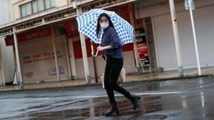 Una mujer en una calle de Suzuka, Japón, antes de la llegada del tifón Hagibis, 12 de octubre de 2019. Es en Suzuka que tiene lugar el  Gran Premio de Fórmula 1, afectado por la tormenta.