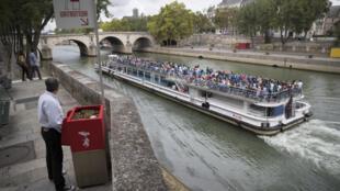 Un hombre orina en un 'uritrottoir' en la Isla Saint-Louis mientras pasa un barco por el Sena.