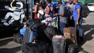 Des Bahaméens montent dans un bus vers un centre d'accueil après avoir été forcés de descendre d'un ferry menant en Floride, le 9 septembre 2019.
