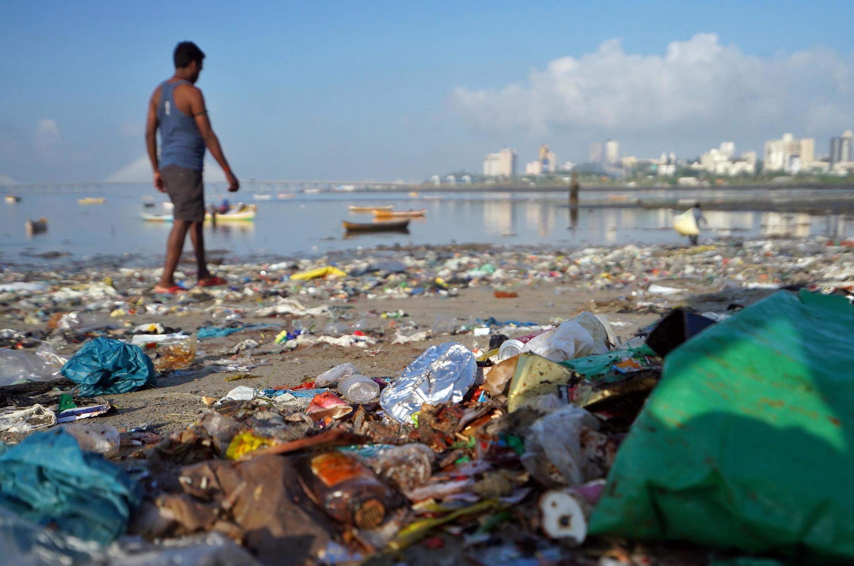 A man walks on a garbage-strewn beach in Mumbai, India, on 2 October, 2019.