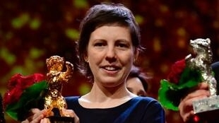 """Romanian director Adina Pintilie holds her Golden Bear for Best Film she was awarded for the movie """"Touch Me Not"""" during the awards ceremony of the 68th edition of the Berlinale film festival on February 24, 2018 in Berlin."""
