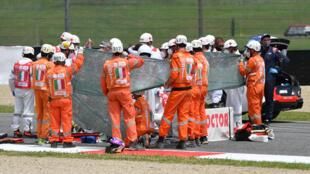Du personnel médical s'occupe du pilote suisse de Moto3 Jason Dupasquier avant son évacuation après une chute lors de la séance de qualification du Grand Prix d'Italie, au circuit du Mugello, au nord-est de Florence, le 29 mai 2021.